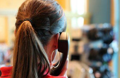 Eine Frau mit einem Telefonhörer am Ohr