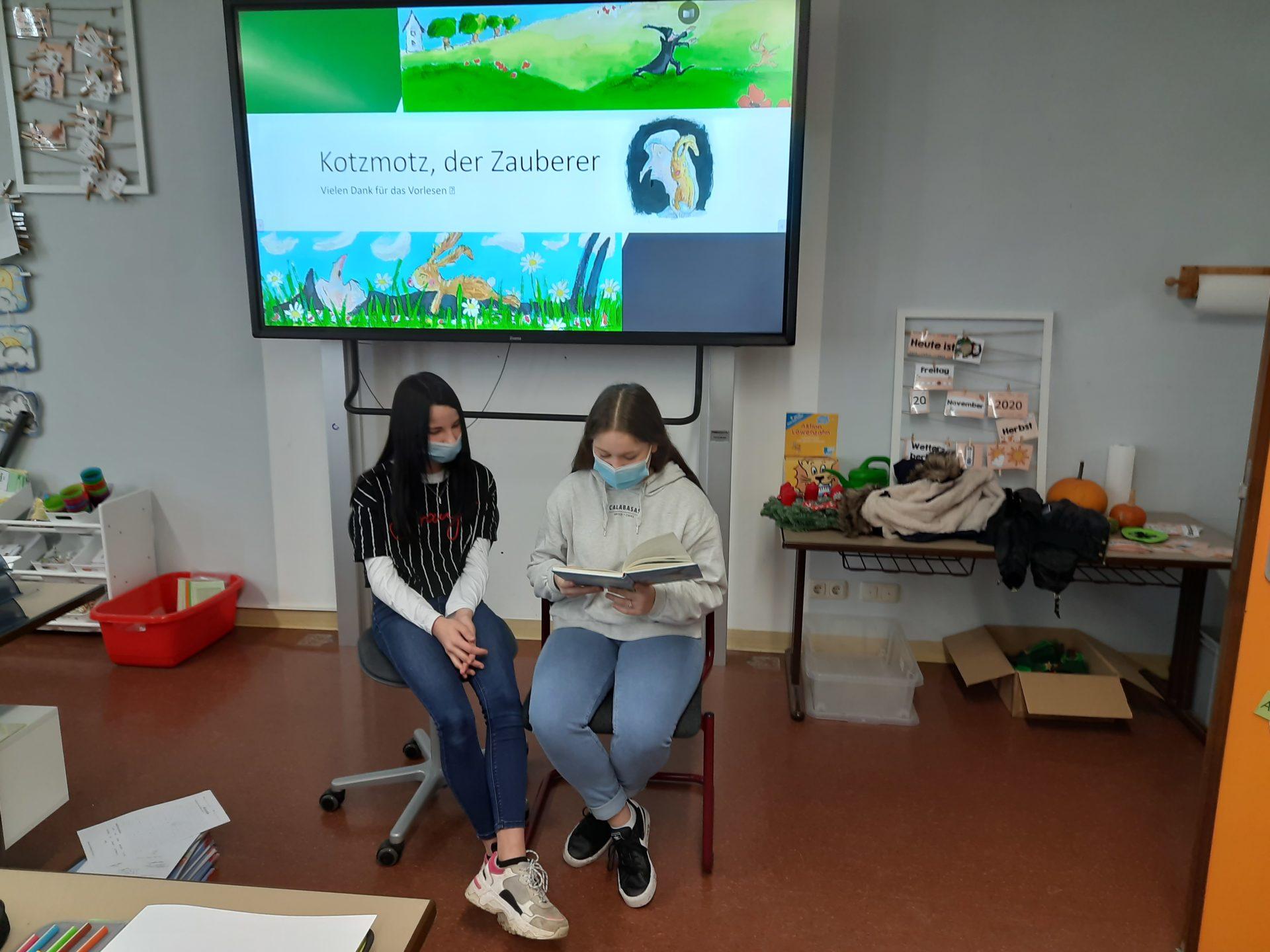 zwei Schülerinnen lesen ein Buch vor